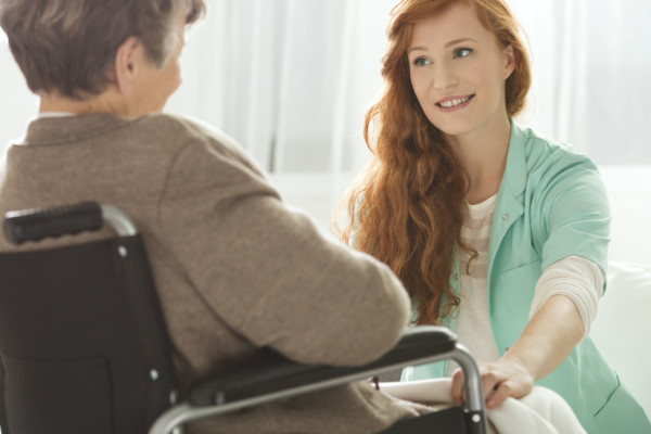 Supportive young nurse looking at elder woman